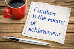 Comfort is the enemy of achievement. Handwriting on a napkin with a cup of espresso coffee Stock Image