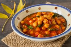 Comfort food, chickpea and spinach vegetarian meal. Homemade rustic chickpea and spinach curry on a table Stock Photography