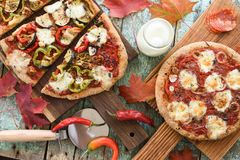 Comfort food. Homemade pizzas with eggplants, peppers, salami an royalty free stock images
