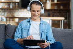 Handsome man trying to concentrate. Comfort pose. Smiling male person wearing headphones and looking at his device while sitting at home Royalty Free Stock Photos