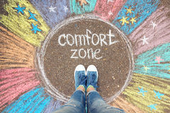 Comfort zone concept. Feet standing inside comfort zone circle. Comfort zone concept. Feet standing inside comfort zone circle surrounded by rainbow stripes Royalty Free Stock Images
