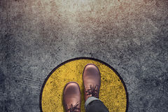 Comfort Zone concept, Male with leather shoes steps over circle. Line to outside bound, Top view and Dark tone, Grunge Dirty Concrete Floor as Background stock photography