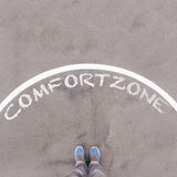 Comfort zone text on asphalt ground, feet and shoes on floor Royalty Free Stock Images