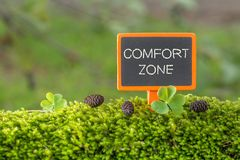 Comfort zone text on small blackboard. Sign on green moss with Clover , blur green tree plant background royalty free stock photography