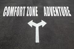 Comfort zone vs adventure choice concept. Two direction arrows on asphalt Stock Photography