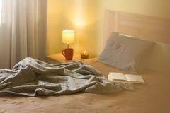 Comfortabel bed met zacht hoofdkussen in ruimtebinnenland stock foto's