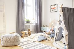 Comfortabel bed in Skandinavische jonge geitjesslaapkamer met grijze tent en grote poef, echte foto met model op de muur stock fotografie