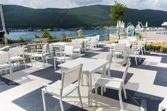 Comfortabel Grieks restaurant met witte lijsten en overzeese mening stock afbeelding