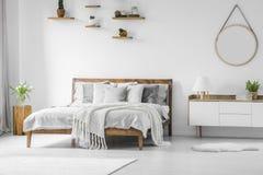 Comfortabel groot houten ontworpen bed met linnen, hoofdkussens en blanke stock afbeeldingen