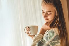 Comfortabel huis Vrouw met kop van hete drank door het venster Het bekijken venster en drinkt thee goedemorgen met thee Het jonge stock foto's