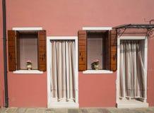 Comfortabel plattelandshuisje met een roze muur en houten blinden en deuren met een klimaat controleren-gordijn royalty-vrije stock afbeeldingen