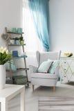 Comfortabel woonkamerbinnenland met leunstoel en modieuze plank stock fotografie