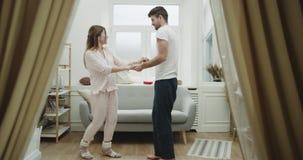 Comfortabele atmosfeer in woonkamerpaar dansen romantisch in pyjama's 4K