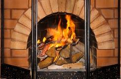 Comfortabele de roosterhout en brand van de baksteenopen haard stock afbeelding