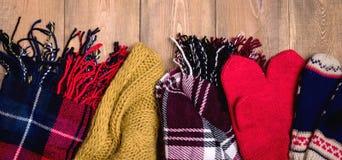 Comfortabele de winter Warme gebreide sjaals en vuisthandschoenen als achtergrond op houten achtergrond met ruimte voor tekst Hoo Stock Foto