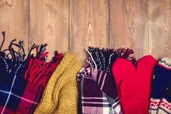 Comfortabele de winter Warme gebreide sjaals en vuisthandschoenen als achtergrond op houten achtergrond met ruimte voor tekst Hoo Stock Afbeelding