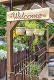 Comfortabele en het uitnodigen tuin met veel installaties en welkom teken royalty-vrije stock foto's