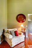 Comfortabele leunstoel met hoofdkussens in de hoek van de woonkamer Stock Foto