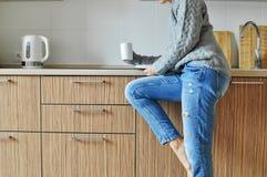 Comfortabele ochtend: het mooie jonge meisje werken en het drinken koffie op een stoel in de keuken in de Skandinavische stijl royalty-vrije stock foto