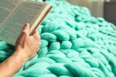 Comfortabele samenstelling, close-up van het boek van de vrouwenlezing op merinoswol p Royalty-vrije Stock Foto