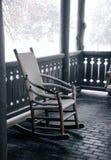 Comfortabele schommelstoel op een luchtige portiek, in de sneeuw Stock Afbeeldingen