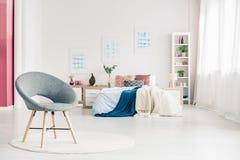 Comfortabele slaapkamer met grijze stoel stock fotografie