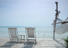 Comfortabele witte ligstoel en hangmat die zeegezicht onder ogen zien Royalty-vrije Stock Foto's