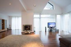Comfortabele woonkamer met grote vensters en open haard Royalty-vrije Stock Afbeeldingen