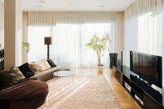 Comfortabele woonkamer met lange bank en TV-reeks royalty-vrije stock fotografie