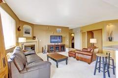 Comfortabele woonkamer met open haard en leerlaag Stock Afbeeldingen