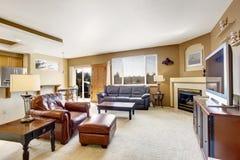 Comfortabele woonkamer met open haard en leerlaag Royalty-vrije Stock Foto's