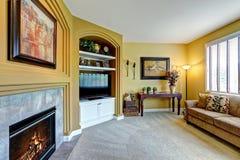 Comfortabele woonkamer met open haard en TV Stock Foto