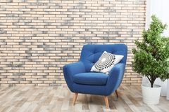 Comfortable armchair with cushion and houseplant. Against brick wall stock photo