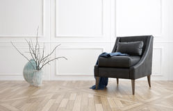 Comfortable armchair in a living room. Comfortable black leather armchair in a minimalist living room interior with white panelled walls, hardwood floor and a Stock Photography