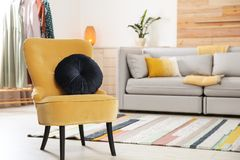 Comfortable armchair with soft cushion in modern living room interior. Space for text stock images