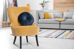 Comfortable armchair with soft cushion in modern living room interior. Space for text royalty free stock photos
