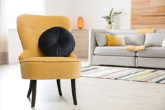 Comfortable armchair with soft cushion in modern living room interior. Space for text stock photos