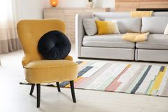 Comfortable armchair with soft cushion in modern living room interior. Space for text royalty free stock image