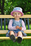 Comfortable baby child. Happy child comfortable sitting on a bench in summer garden, cute girl eating pea outdoor Stock Photography