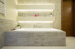 Comfortable bath. Illuminated comfortable bath in luxury bathroom Stock Image