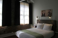 Comfortable bed, with brick walls and cool accents, The Old No. 77 Hotel & Chandlery, New Orleans, 2016. Welcoming scene of comfy beds, bricks walls, cool Stock Photos