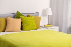 Comfortable bed with cushions. In room Stock Image