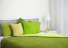 Comfortable bed with cushions. In room Royalty Free Stock Photography