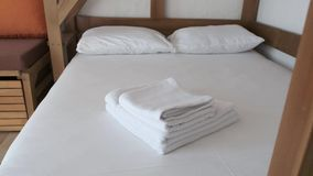 A comfortable bed with white sheets, towels and pillows in a hotel room is waiting for new vacationers. A comfortable bed with white clean sheets, towels and stock footage