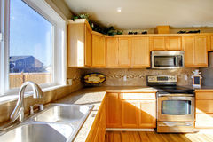 Comfortable big kitchen room. Big kitchen room with wooden cabinets and steel appliances royalty free stock photos