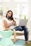 Comfortable breakfast with laptop. Portrait of beautiful girl having comfortable breakfast of coffee and croissant, in armchair with laptop computer Royalty Free Stock Photos