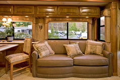 Comfortable camper interior. A comfortable camper interior design, leather sofa with cushions, camp site seen through the windows Stock Photo