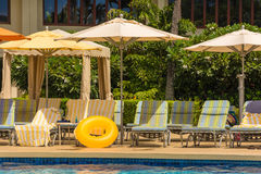Comfortable chaise lounges by the swimming pool Stock Photography