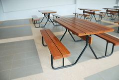 Comfortable and clean canteen with fix seat tables and chairs. Comfortable wood and steel fix seat canteen tables and chairs. Row of wooden top fast food royalty free stock photography
