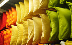 Comfortable colorful fabric cushions on modern store shelves.  Royalty Free Stock Images